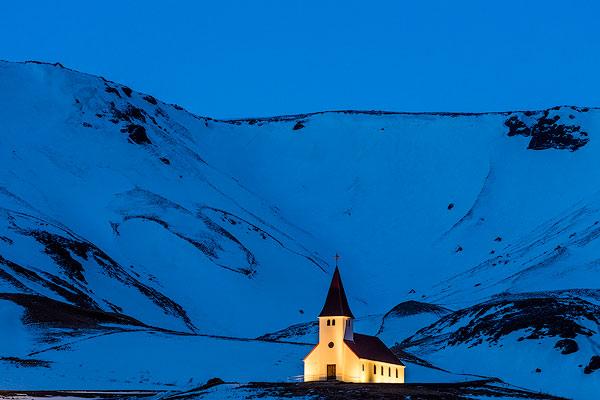 Vik i Myrda church lit up at dusk in Vik, Iceland