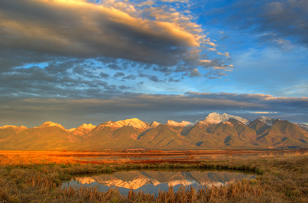 Pond at the Ninepipe NWR reflects dramatic light of the Mission Mountains in Montana