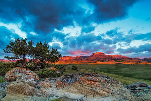 Fiery sunrise light strikes Ear Mountain along the Rocky Mountain Front near Choteau, Montana
