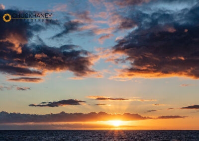 Sunset over the Pacific Ocean from tour boat in Kauai, Hawaii, USA